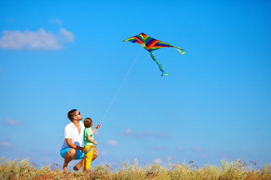 Father and son playing with kite outside